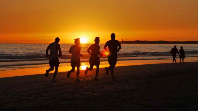 Laufen am Strand beim Untergang der Sonne