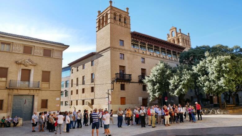 Besuchergruppe vor der Kathedrale mit dem Rathaus von Huesca im Hintergrund